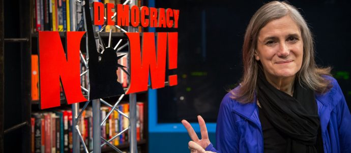 democracy now reporter next to sign
