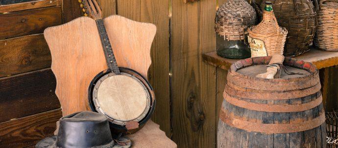 banjo, cowboy hat, bottles and barrel